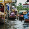 Each of them is squeezed into a similar-looking wooden boat, which carries them through endless waterways of the market.