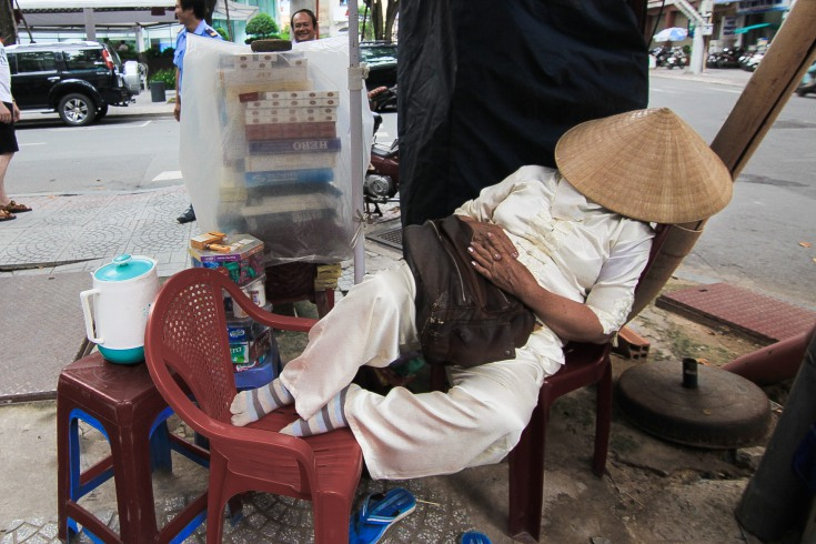 An owner of the cigarettes stand blissfully snoring under the shelter of his cane-woven hat.