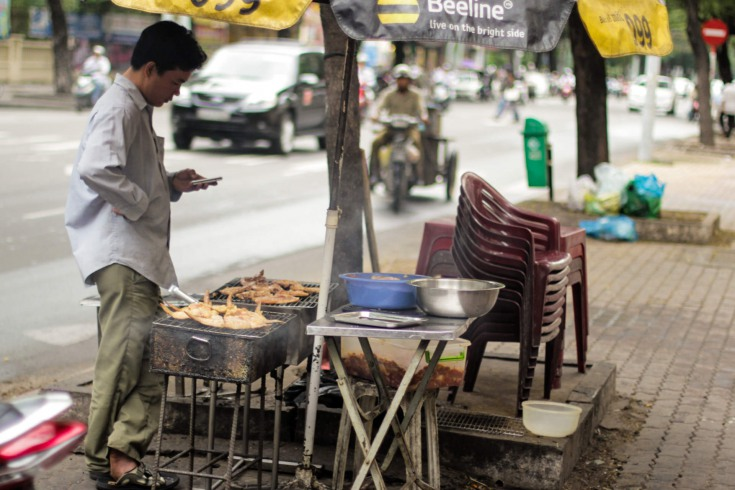 On a makeshift, tiny, portable grill a hawker barbeques meat and seafood.