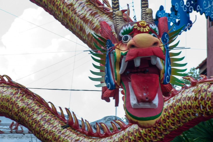 The gaping, frozen in a silent roar muzzle greets in Malacca's Chinatown.
