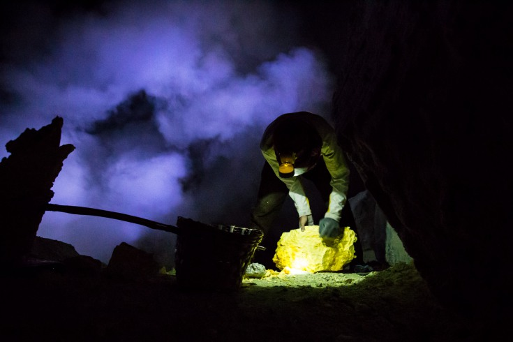 Miners tightly cover faces with scarfs against the acid vapours and load the gold-orange rocks into wicker baskets connected with a bamboo stick.