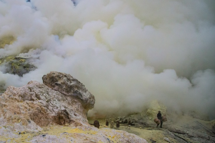 In pale lights of flashlights, between the flames and thick clouds of sulphurous smoke, dark silhouettes of sulphur miners move around