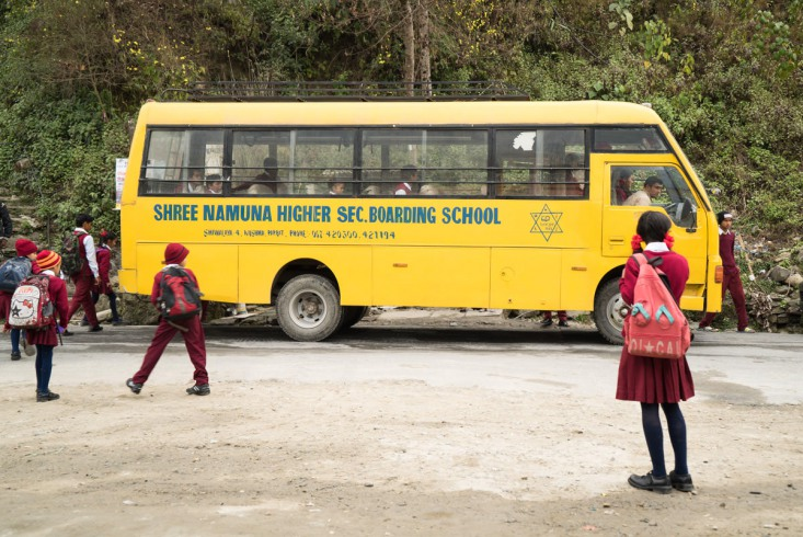 A cloudy, chilly morning in February. A group of children runs to a school bus parked at the side of the sandy road.