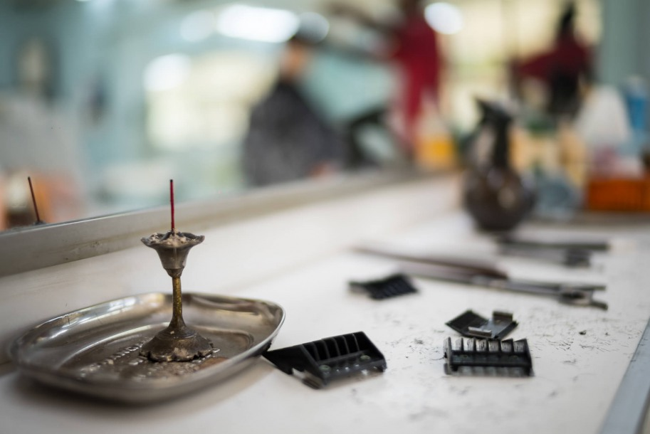 Next to the Indian incense, on the white wooden counters, traditional and modern hairdressing tools lie side by side.