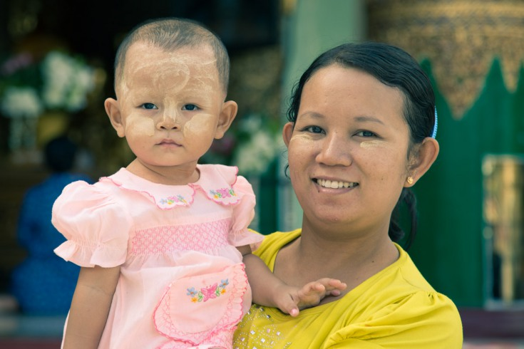 Young parents and their children with faces smudged with sun-screening thanaka paste and shaved heads – for the hair to grow stronger and for a cooling effect.