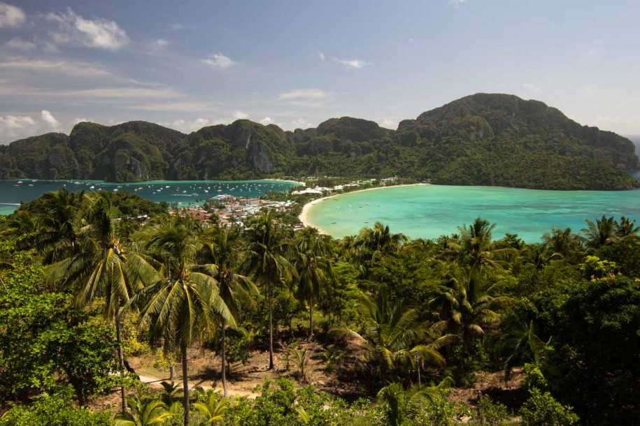 A wall of green palm trees – reaching to the sky – morphs into a narrow isthmus connecting the opposite ends of Phi Phi Don.