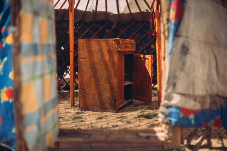 Some furniture stands patiently between the fabrics: a metal bed with an old mattress, a few small wooden cabinets and a stove that will be placed in the centre of the construction.