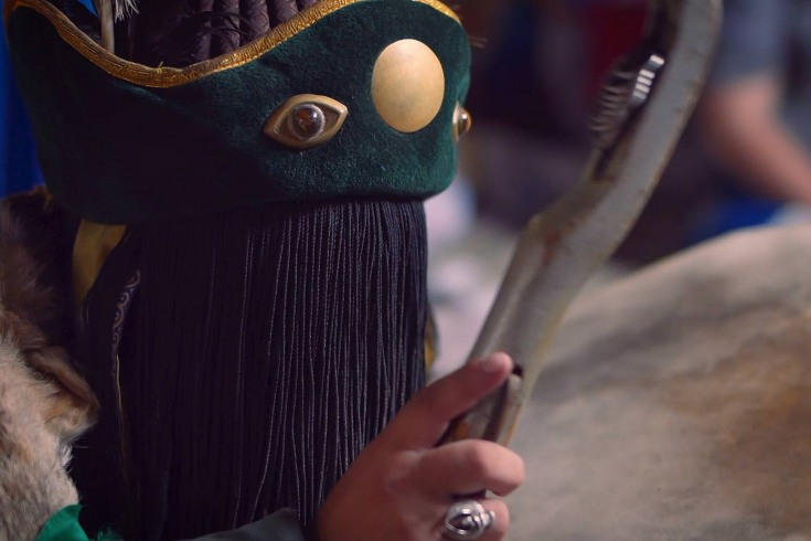 A man, huddled on a low stool, rhythmically beats a large leather drum.